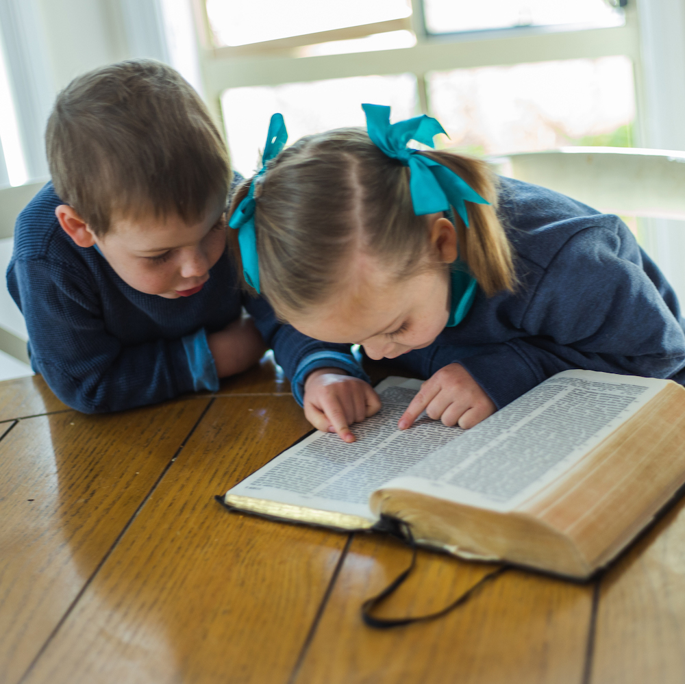 Two young children reading the Bible
