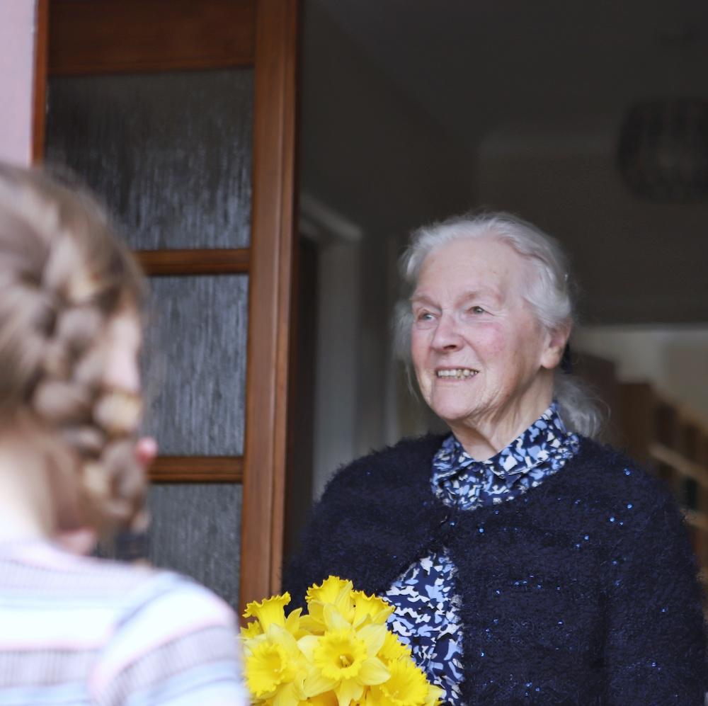 Young girl delivering flowers to elderly neighbour